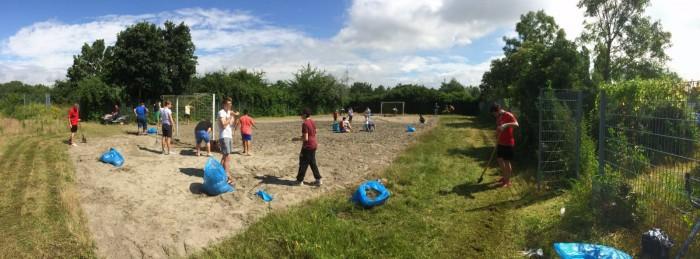 Handballer reinigen das Beachfeld